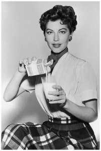 ava1955-portrait-of-american-actor-ava-gardner-wearing-a-plaid-skirt-and-a-short-sleeved-blouse-while-pouring-a-glass-of-milk-photo-by-hulton-archivegetty-images