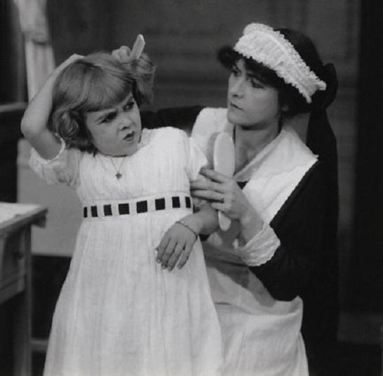 Fanny Cossar in the role of the maid in Unto the Least of These. (combing the hair of the young star of the film, Mary McAllister)