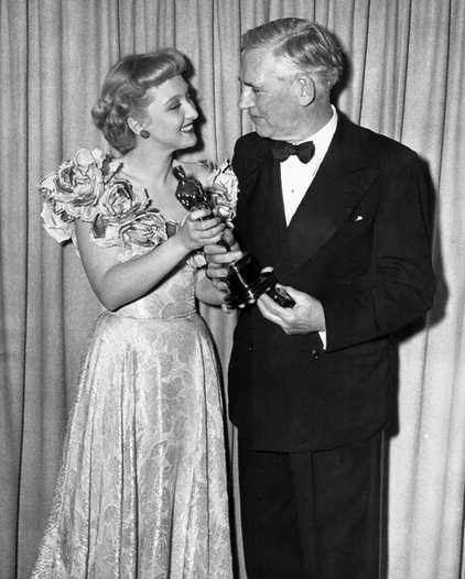 "Celeste Holm presenting the Oscar for Best Supporting Actor to Walter Huston for his portrayal of ""Howard"" in The Treasure of Sierra Madre"